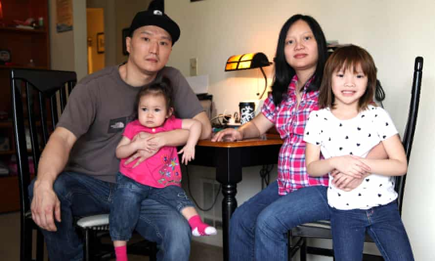 Adam Crapser poses with daughters and wife in the family's living room in Vancouver, Washington, in 2015.