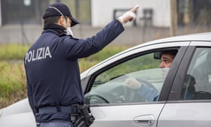 A police officer wearing a protective mask speaks with a motorist at a yellow zone quarantine roadblock, near the red zone in the town of Codogno