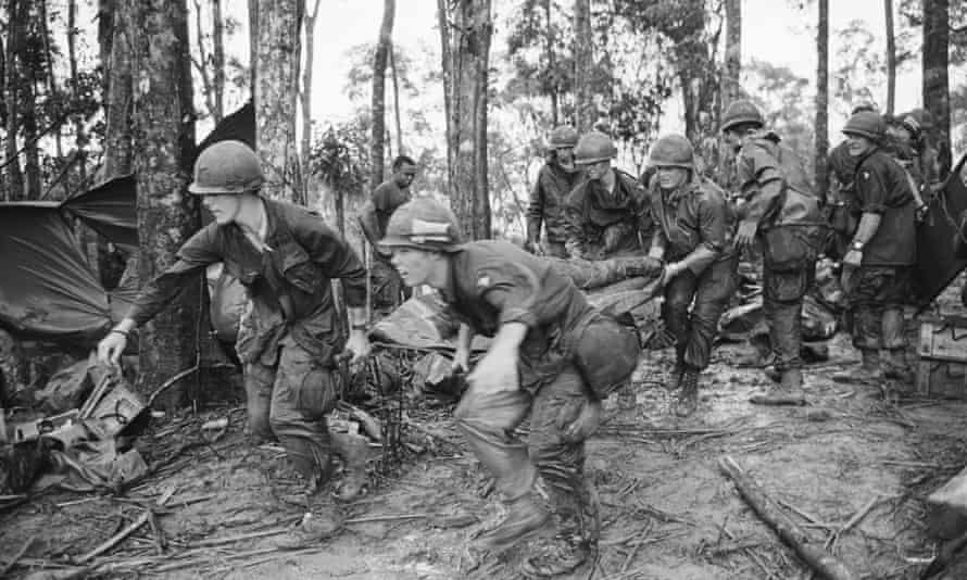 A quartet of U.S. 101st Air Division troopers keep low as they rush a stretcher-borne wounded comrade to a medical aid station during the battle for Hamburger Hill.