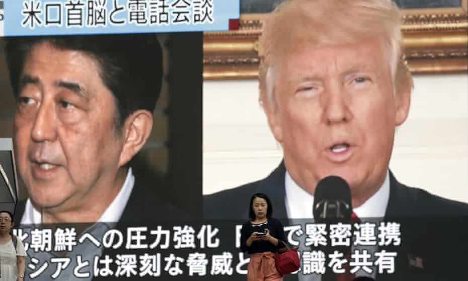 In Tokyo, people walk past a news broadcast showing Japanese prime minister Shinzo Abe and US president Donald Trump following North Korea's nuclear test.