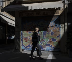 A woman walking in central Athens as Greece saw a record-breaking rise in the number of confirmed coronavirus cases for the second consecutive day.