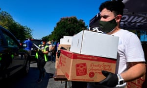 Volunteers help load a vehicle with boxes of food at a food bank in the Los Angeles County city of Duarte, California on 8 July 2020 as the record for most coronavirus cases in a single day is set in California.