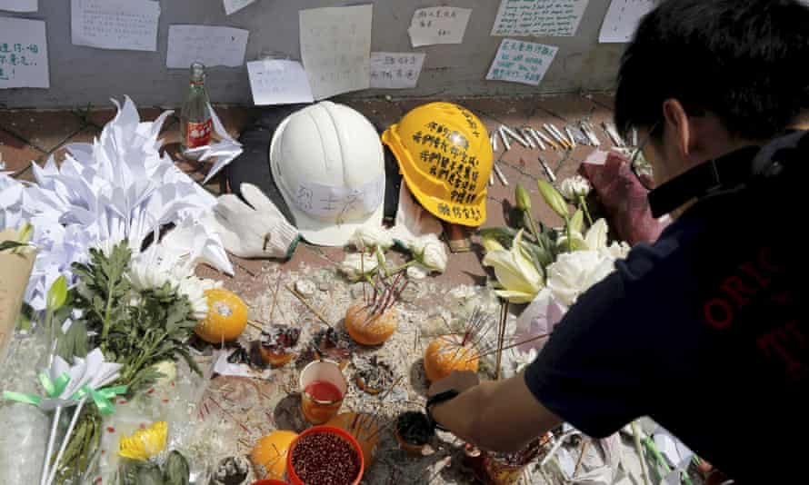 Mourners stop by a makeshift memorial to a protester who fell to his death on Saturday.