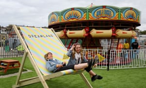 Visitors relax in a giant deck chair at the Dreamland Margage amusement park, behind is a merry-go-round. Kent, UK.
