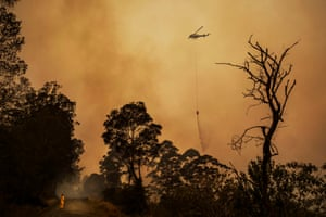 A helicopter drops water on a fire racing up a steep gully with houses nearby in Killabakh, NSW, in November