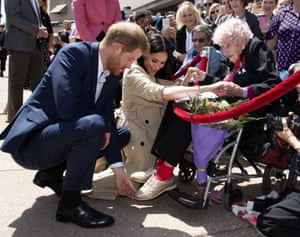 Britain's Prince Harry and Meghan, Duchess of Sussex meet 97-year-old Dafney Dunne during a walk about outside the Opera House in Sydney, Australia, Tuesday, Oct. 16, 2018. Prince Harry and his wife Meghan are on a 16-day tour of Australia and the South Pacific (Paul Edwards/Pool via AP)