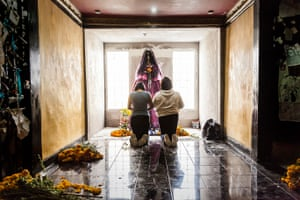 A couple kneel in prayer to La Nina Blanca (The White Lady), one of the many pseudonyms for Santa Muerte in Pachuca, in Hidalgo State, Mexico.