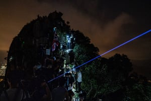 Pro-democracy supporters wave laser pointers, phones and lanterns as they gather on Lion Rock.