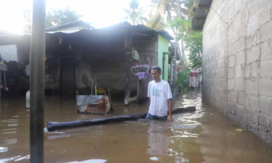 Kanisius Elo walks in floodwaters in Tasi-Tolu, a suburb in the north-west of Dili, the capital of Timor-Leste.