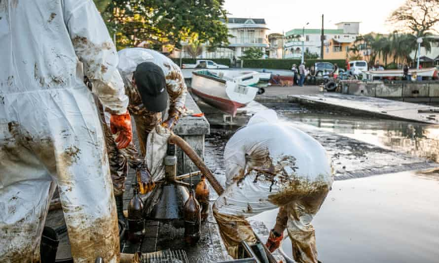 Fishermen and skippers with a makeshift oil extraction device at the Mahébourg waterfront in Mauritius.