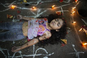 A girl lies surrounded by candles and designs of white powder. Believers often ask for spiritual healing or protection from witchcraft, or thank the goddess for curing an illness
