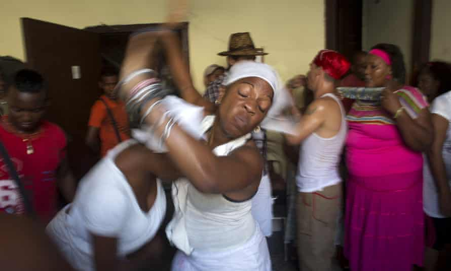Santeria practitioners undergo a brief fit of spirit-induced convulsions during a ceremony to attract spirits of dead ancestors to ask for guidance in downtown Havana last month.