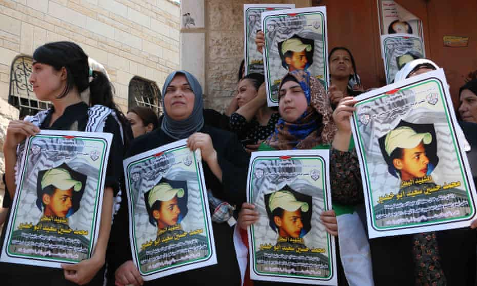 Relatives of Mohammed Abu Khdeir hold pictures of the boy outside his home during the funeral in July 2014.