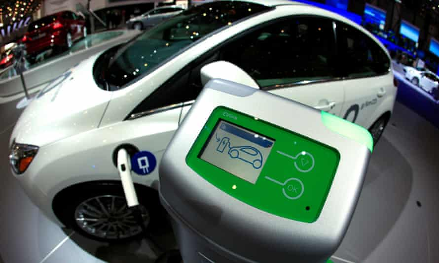 A Ford Focus electric car is displayed next to its charging station.