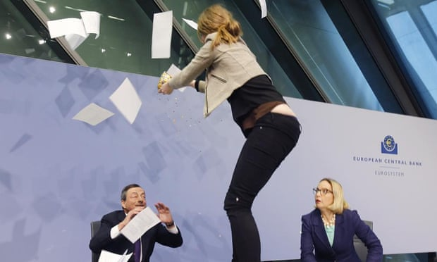 An activist throws papers at the ECB president, Mario Draghi, left, in Frankfurt, Germany. Photograph: AP