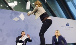 A Femen activist stands on the table of the podium throwing paper at ECB President Mario Draghi, left, during a press conference of the European Central Bank, ECB, in Frankfurt, Germany, Wednesday, April 15, 2015.