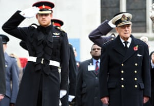 Britain's Prince Harry salutes as he stands alongside his grandfather Britain's Prince Philip, Duke of Edinburgh, during their visit to the Field of Remembrance at Westminster Abbey in central London