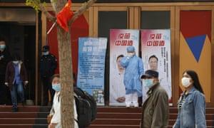 یک کارگر پزشکی جمعه ، 9 آوریل 2021 ماسک خود را در نزدیکی تابلوهای تبلیغاتی که متخصص پزشکی مشهور چینی ، ژونگ نانشان و کلمات