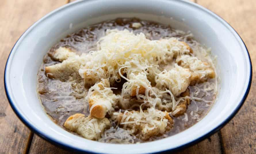 A white bowl of French onion soup with grated cheese on top