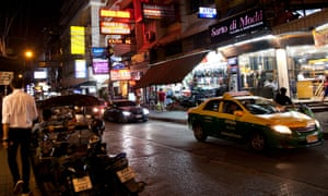 Sukhumvit Road at Night in Bangkok - Thailand. Neon street signs, taxis and cars on the road and busy sidewalks.