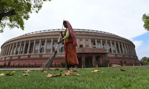 A worker cleans the lawn at Parliament House.