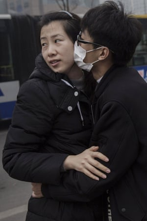A man wears a mask as he kisses his partner