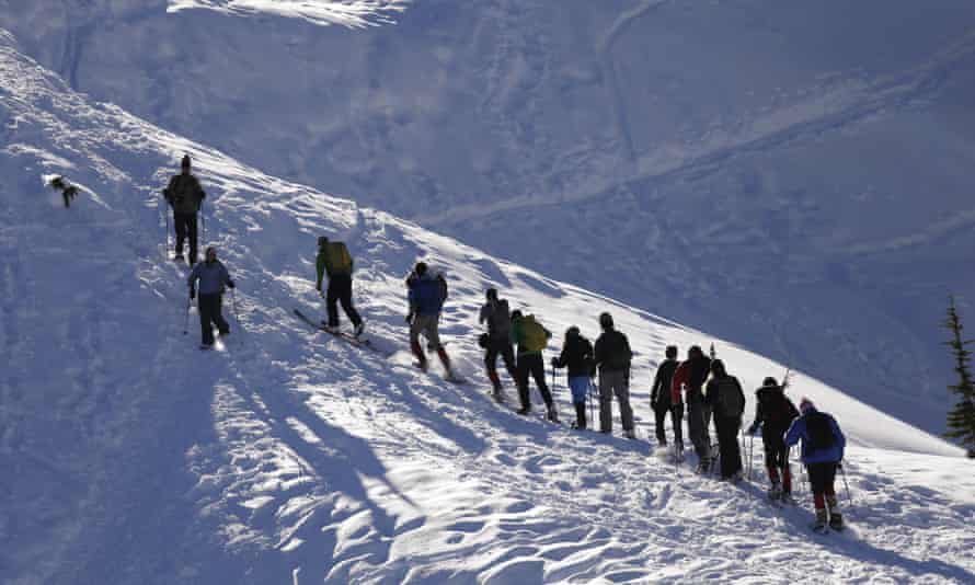 Students and instructors head up a hill on snowshoes during an avalanche awareness field trip for teenagers, at Mount Baker, Wash.