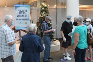 People wait in a line on New Year's Eve to receive a COVID-19 vaccination at a site for seniors in an unoccupied store at the Oviedo Mall.