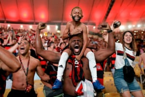 Flamengo fans cheer a goal scored by Gabriel Barbosa against Argentina's River Plate in the Copa Libertadores final, broadcast on a giant screen at the Macarena stadium in Rio de Janeiro.