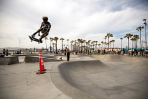 Skateboarders perform tricks during a heatwave at Venice Beach in Los Angeles, California