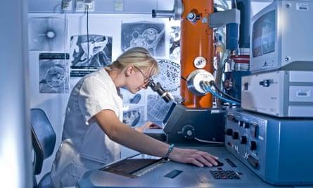 Female laboratory technician working on an electron microscope