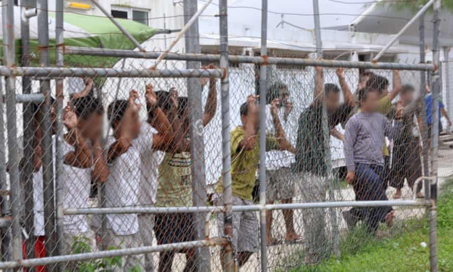 asylum seekers behind a fence on Manus Island