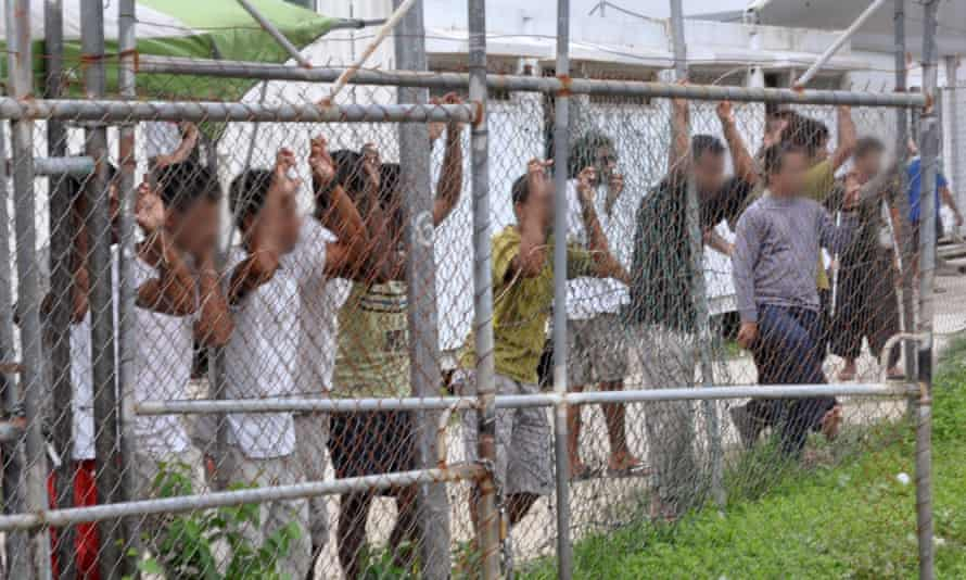 Asylum seekers stand behind a fence at the Manus Island detention centre in Papua New Guinea.