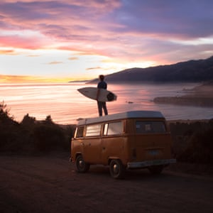 James Barkman standing on top of his VW van and holding a surfboard as the sun sets on the coastline of Big Sur, California, US