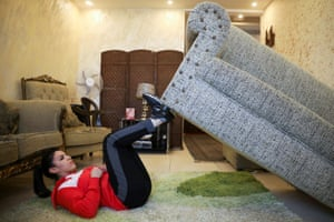 Olympic hopeful judoka Hadeel Alami uses her family's sofa as a part of her training at home in Amman, Jordan.