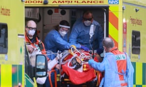Medical staff transfer a patient from an ambulance to the Royal London hospital.