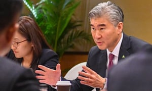 Sung Kim talks with members of the North Korean delegation during a working group meeting before the summit.