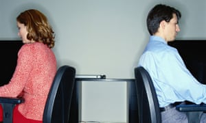 woman and man sitting at desks with backs to each other