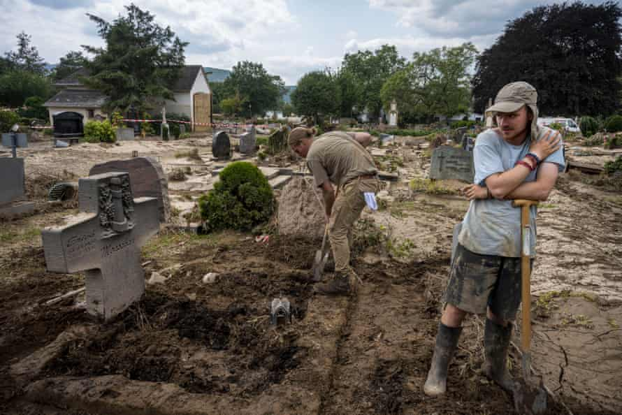 Benjamin Monschau, right, and his assistant Johannes Ehmer remove hard clay from their grandfather's grave