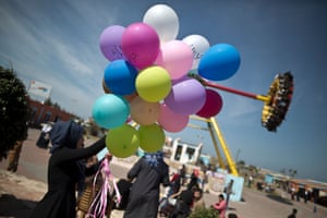 A Palestinian woman holds balloons, some reading in Arabic 'women's rights', during an event organised by the United Nations