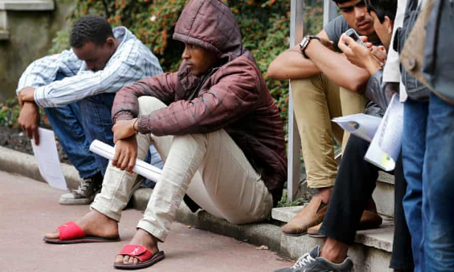 Migrants claiming asylum gather outside the government office in Calais.