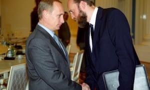 Vladimir Putin shakes the hand of the oligarch Sergei Pugachev