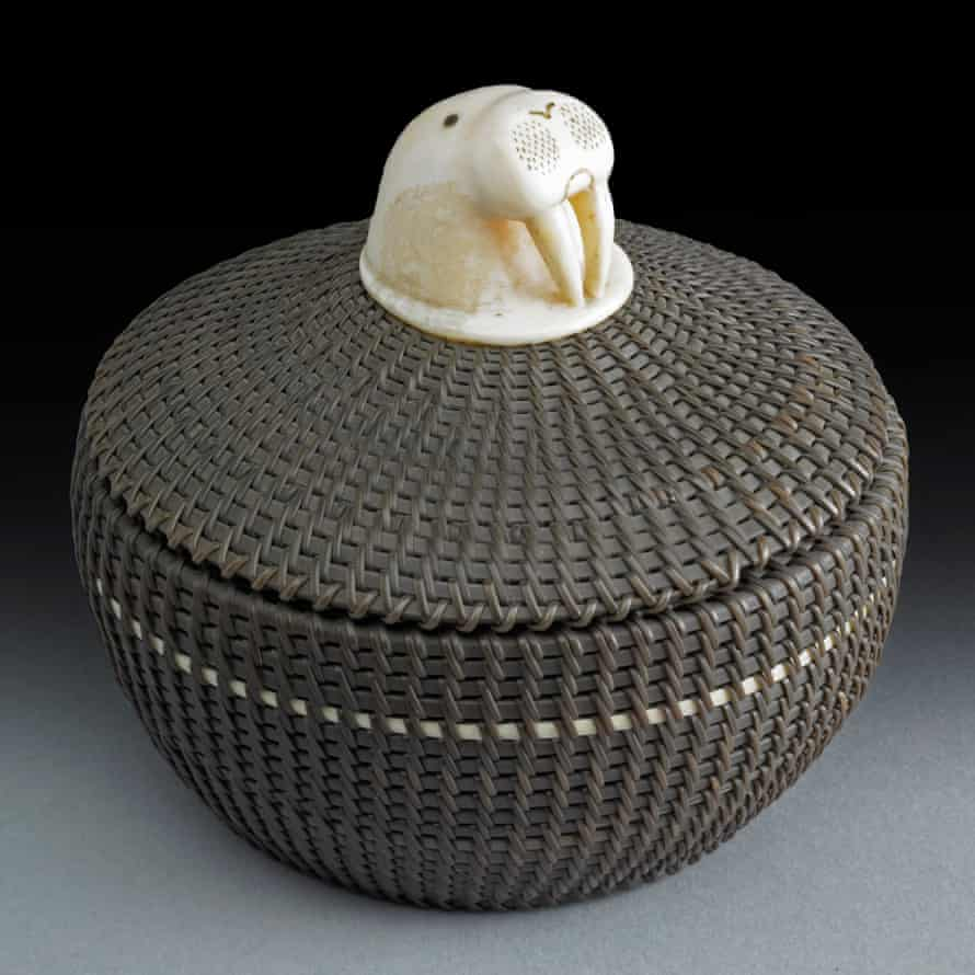 A round, coiled basket with carved decoration on the lid in the form of a walrus head with tusks by Marvin Peter, Alaska, 1952.