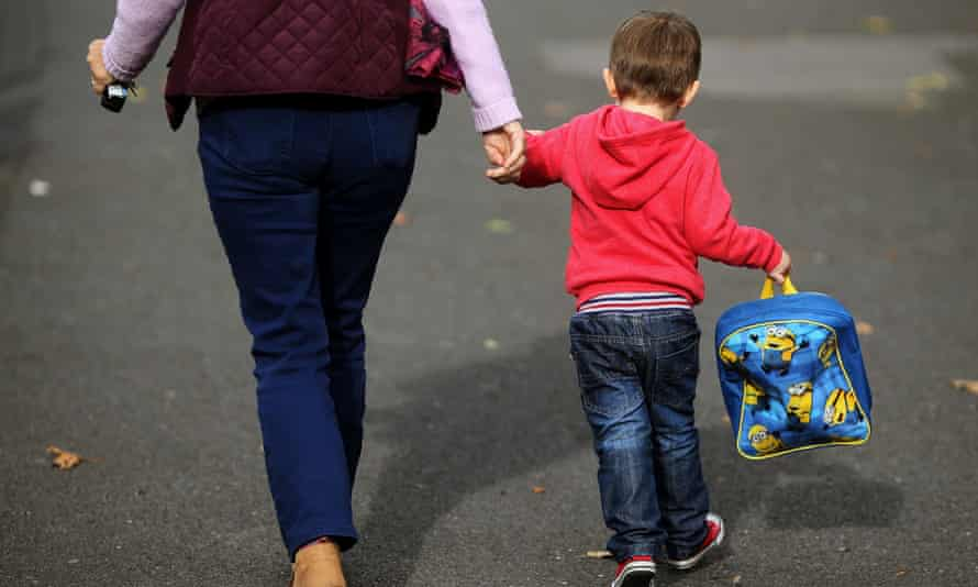 An adult is holding a young child's hand, who is carrying a schoolbag
