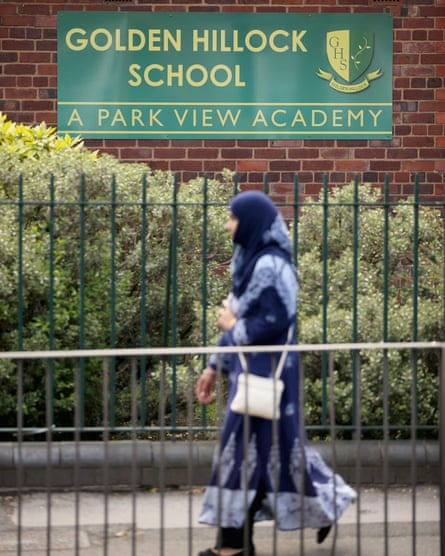 woman in headscarf walking past Golden Hillock sign