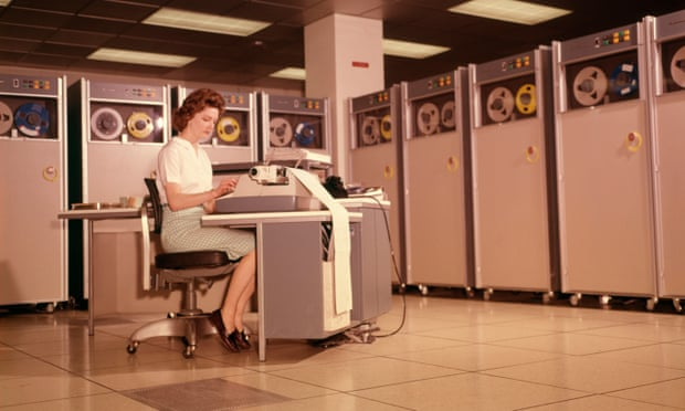 A woman uses a computer in the 1960s.