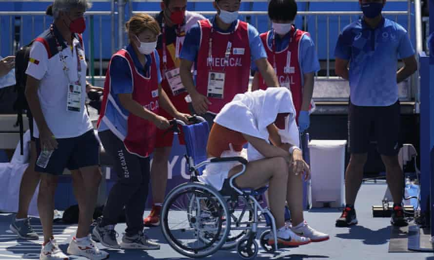 Paula Badosa, of Spain, is helped off the court in a wheelchair having suffered heat exhuastion.