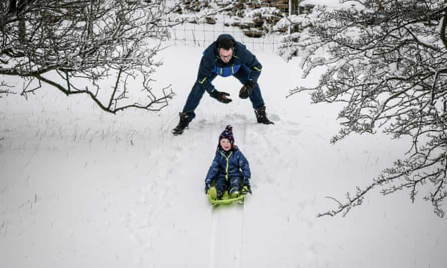 Kids make the most of the drifting snow on the Cotswold hills, Worcestershire, December 2017.