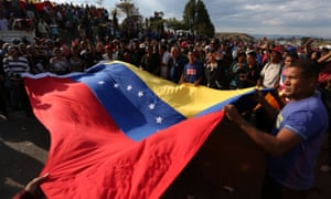 People hold Venezuela's national flag during a pro-government rally at the border between Venezuela and Brazil.