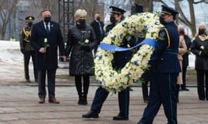 Health workers carry a wreath as Quebec Premier Francois Legault, left, and his wife Isabelle Brais look on during a ceremony for the victims of COVID-19.